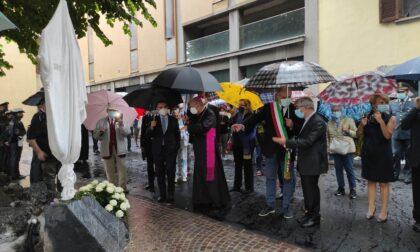 """Il piazzale dove fu ucciso un anno fa, da oggi intitolato a don Roberto Malgesini. Il sindaco, sotto la pioggia: """"Anche il cielo piange"""""""